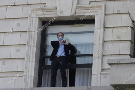 """Fairmont San Francisco hotel manager Jacco van Teeffelen wears a mask while standing on a ledge at the hotel during a singing of the Tony Bennett song """"I Left My Heart in San Francisco,"""", in San Francisco. Bennett had encouraged San Franciscans to join him in a sing-a-long from their homes during shelter in place orders for COVID-19 concerns"""