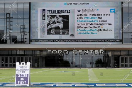 Sign sits on a artificial field frequented by fans at the Ford Center by The Star, the Dallas Cowboys headquarters and training facility, as a large video screen on the exterior wall of the building broadcast the team's latest selection in the NFL football draft in Frisco, Texas