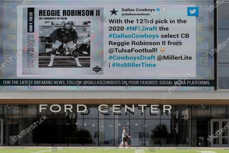 Couple walks in front of the Ford Center at The Star, the Dallas Cowboys headquarters and training facility, as a large video screen on the exterior wall of the building broadcast the team's latest selection in the NFL football draft in Frisco, Texas
