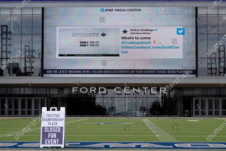 Sign sits on a artificial field frequented by fans at the Ford Center by The Star, the Dallas Cowboys headquarters and training facility, as a large video screen on the exterior wall of the building broadcast the team's most recent news developing from the NFL football draft in Frisco, Texas