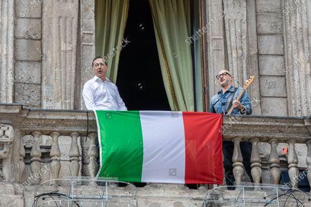 Milan Mayor Giuseppe 'Beppe' Sala (L) and Italian musician Saturnino (Saturnino Celani) singing the popular protest song 'Bella ciao' from the balcony of Palazzo Marino (Milan's city hall)