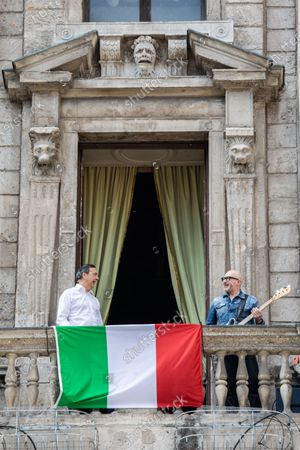 Stock Picture of Milan Mayor Giuseppe 'Beppe' Sala (L) and Italian musician Saturnino (Saturnino Celani) singing the popular protest song 'Bella ciao' from the balcony of Palazzo Marino (Milan's city hall)