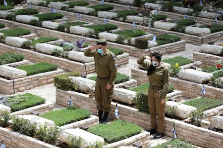 Israeli soldiers salute after decorating the graves of fallen Israeli soldiers at the Mount Herzl (Mount of Remembrance) military cemetery in Jerusalem, Israel, 26 April 2020. Israel is preparing to mark its 'Day of Remembrance for the Fallen Soldiers of Israel and Victims of Terrorism', which will begin at sunset on 27 April 2020. For the first time in Israel history, bereaved families will not be allowed to enter the cemetery on Memorial Day for fear of mass infection and spread of the coronavirus and COVID-19 disease