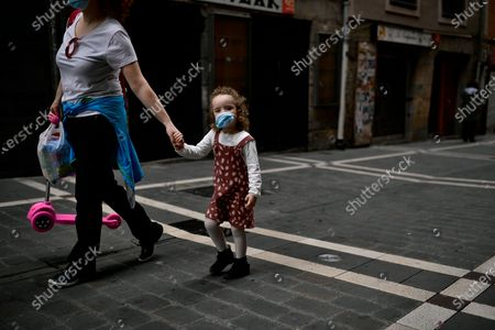 Irati, a little girl, 3 years old, wears face mask to prevent the coronavirus while she's going for a walk with her mother, Montse Fernandez, in Pamplona, northern Spain, . On Sunday, children under 14 years old will be allowed to take walks with a parent for up to one hour and within one kilometer from home, ending six weeks of compete seclusion