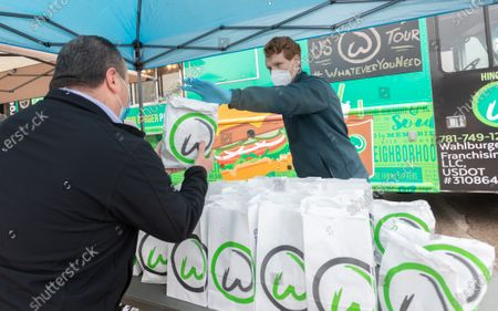 Representative Joseph P Kennedy III (D-MA) joins chef Paul Wahlberg to distributes a free Whalburgers meal to Teamsters Local 25 member who drive for UPS
