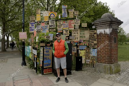 Artist and local resident Peter Liversidge poses for photographs in front of his signs supporting the National Health Service (NHS) during the coronavirus outbreak, after he made and put them up on railings gradually for the last three weeks in a work he calls 'Sign Paintings for the NHS' in east London, . The highly contagious COVID-19 coronavirus has impacted on nations around the globe, many imposing self isolation and exercising social distancing when people move from their homes