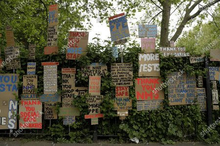 Signs supporting the National Health Service (NHS) during the coronavirus outbreak, displayed together on railings after being made and put up there gradually for the last three weeks by artist and local resident Peter Liversidge in a work he calls 'Sign Paintings for the NHS' in east London, . The highly contagious COVID-19 coronavirus has impacted on nations around the globe, many imposing self isolation and exercising social distancing when people move from their homes