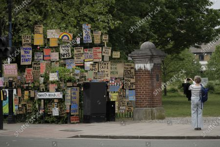 Woman takes a picture of signs supporting the National Health Service (NHS) during the coronavirus outbreak, displayed on railings after being made and put up there gradually for the last three weeks by artist and local resident Peter Liversidge in a work he calls 'Sign Paintings for the NHS' in east London, . The highly contagious COVID-19 coronavirus has impacted on nations around the globe, many imposing self isolation and exercising social distancing when people move from their homes