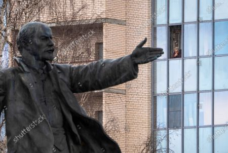 An elderly woman stands at a window of her apartment in Kirovsk, about 30 kilometres (19 miles) east of St.Petersburg, Russia, with a statue of Soviet Union founder Vladimir Lenin in the foreground. Local authorities ordered residents over 65 and those suffering from certain chronic conditions to stay home to reduce the risk of them contracting the new coronavirus