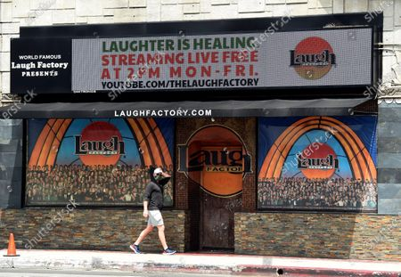 "A pedestrian walks underneath a marquee advertising a ""Laughter is Healing"" stand-up comedy livestream event at the Laugh Factory in Los Angeles. With comedy clubs closed and concert tours put on hold, comics like Craig Robinson, Tiffany Haddish, Will C and others are keeping the jokes flowing on webcasts and Zoom calls even without the promise of a payday, because they say the laughs are needed now more than ever"