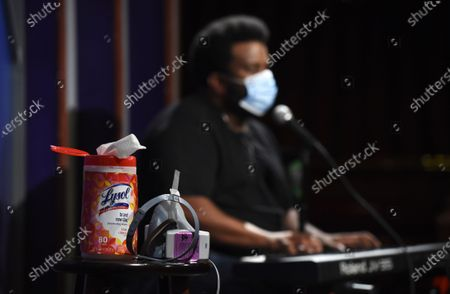 "A bottle of Lysol disinfectant wipes sits on a table onstage as comedian Craig Robinson performs during a ""Laughter is Healing"" stand-up comedy livestream event at the Laugh Factory in Los Angeles. With comedy clubs closed and concert tours put on hold, comics like Robinson, Tiffany Haddish, Will C and others are keeping the jokes flowing on webcasts and Zoom calls even without the promise of a payday, because they say the laughs are needed now more than ever"
