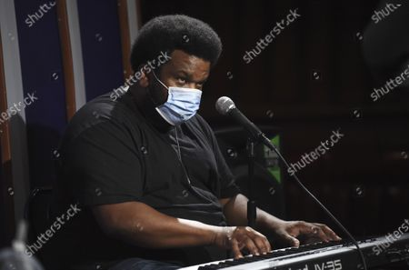 "In this April 20, 2020, photo, comedian Craig Robinson wears a mask as he plays the keyboard during a ""Laughter is Healing"" stand-up comedy livestream event at the Laugh Factory comedy club, in Los Angeles. With comedy clubs closed and concert tours put on hold, comics like Robinson, Tiffany Haddish, Will C and others are keeping the jokes flowing on webcasts and Zoom calls even without the promise of a payday, because they say the laughs are needed now more than ever"