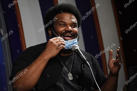 "Stock Photo of Comedian Craig Robinson lowers his mask as he performs during a ""Laughter is Healing"" stand-up comedy livestream event at the Laugh Factory comedy club in Los Angeles. With comedy clubs closed and concert tours put on hold, comics like Robinson, Tiffany Haddish, Will C and others are keeping the jokes flowing on webcasts and Zoom calls even without the promise of a payday, because they say the laughs are needed now more than ever"