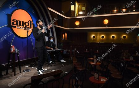 "Comedians Tehran Von Ghasri, left, and Craig Robinson perform to a near-empty room during a ""Laughter is Healing"" stand-up comedy livestream event at the Laugh Factory, in Los Angeles"