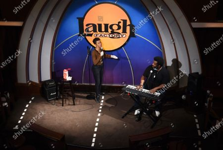 "Comedians Daphnique Springs, left, and Craig Robinson perform together onstage during the ""Laughter is Healing"" stand-up comedy livestream event at the Laugh Factory, in Los Angeles. The white lines on the stage are meant to give the performers a distancing guide"