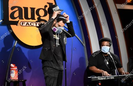 "Stock Picture of Comedian Tehran Von Ghasri, left, takes off his mask to perform alongside Craig Robinson onstage at a ""Laughter is Healing"" stand-up comedy livestream event at the Laugh Factory, in Los Angeles"