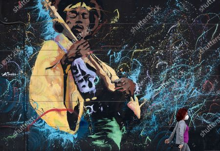 A woman wearing a face mask is seen walking past front a graffiti depicting legend singer and guitarist Jimi Hendrix amid the coronavirus crisis. Following the confinement decreed by the Spanish government and to be extend until 10th May, an exceptional situation of unusual urban scenes such as empty streets or bars, restaurants and shops closed has been caused.