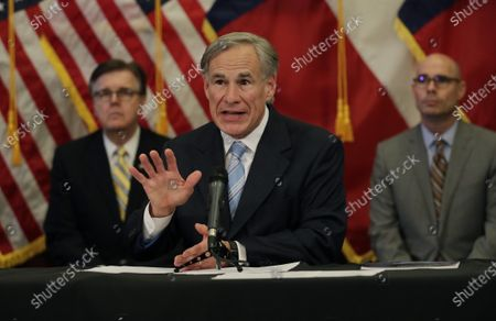 Texas Gov. Greg Abbott, center, with Lt. Gov. Dan Patrick, left, and Texas House Speaker Dennis Bonnen, right, speaks during a news conference where he announced he would relax some restrictions imposed on businesses due to the COVID-19 pandemic, in Austin, Texas