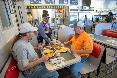 Stock Picture of Coworkers Hugh Kleiman (L) and Kevin Wallace (R) are given their plates at a Waffle House restaurant in Atlanta, Georgia, USA, 27 April 2020. Georgia Governor orders allowed for the reopening of inside dining restaurants and movie theaters in Georgia as the coronavirus COVID-19 pandemic continues.