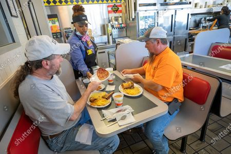 Coworkers Hugh Kleiman (L) and Kevin Wallace (R) are given their plates at a Waffle House restaurant in Atlanta, Georgia, USA, 27 April 2020. Georgia Governor orders allowed for the reopening of inside dining restaurants and movie theaters in Georgia as the coronavirus COVID-19 pandemic continues.