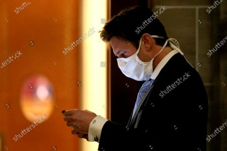 Stock Image of State Rep. David Gregory, R-St. Louis County, wears a protective mask as he checks his phone before entering the House chamber join lawmakers considering the state budget, in Jefferson City, Mo. The House began debate on the budget for the upcoming fiscal year, a daunting task amid declining revenue because of the coronavirus