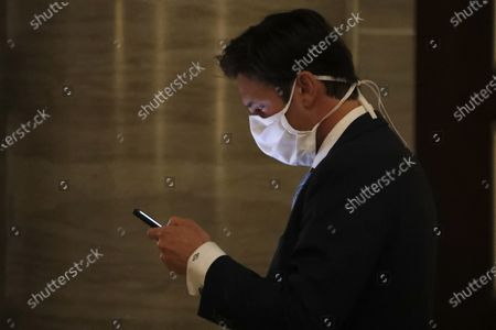 Stock Photo of State Rep. David Gregory, R-St. Louis County, wears a protective mask as he checks his phone before entering the House chamber join lawmakers considering the state budget, in Jefferson City, Mo. The House began debate on the budget for the upcoming fiscal year, a daunting task amid declining revenue because of the coronavirus