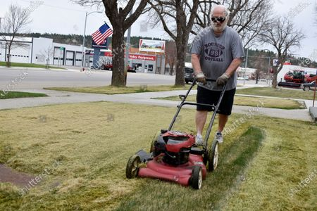Tom Hagstrom mows the grass of St. Benedict's Catholic Church along Main Street in Roundup, Mont. on . Most stores in the small town were considered essential businesses and stayed open despite a month-long closure order over the coronavirus that was lifted this week