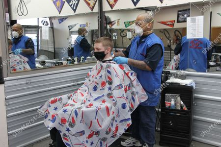 Larry Love, right, the manager at Hair Doctors in Anchorage, Alaska, gives an airman a haircut on . The first signs of activity returned to Alaska's largest city Monday as businesses like hair salons and restaurants slowly began reopening following closures because of the coronavirus
