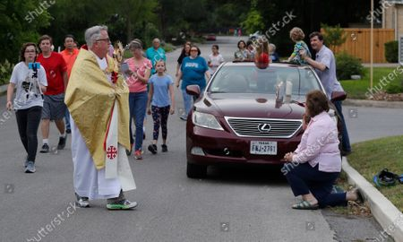 Using social distancing due to the COVID-19 pandemic, the Rev. Pat O'Brien of St.Pius X Catholic Church leads a Eucharist procession through a neighborhood near his church in San Antonio, . Texas Gov. Greg Abbott said churches and other places of worship will be able to expand capacity as long as they continue to use safe distancing practices