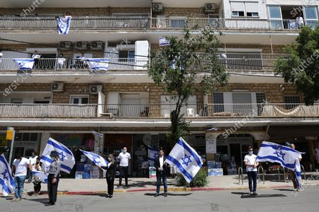 People holding Israeli national flags stand for a moment of silence on as sirens sound throughout the country to mark  'Day of Remembrance for the Fallen Soldiers of Israel and Victims of Terrorism', in Jerusalem, Israel, 28 April 2020. Israel marks its 'Day of Remembrance for the Fallen Soldiers of Israel and Victims of Terrorism' amid the spread of the coronavirus pandemic and COVID-19 disease.