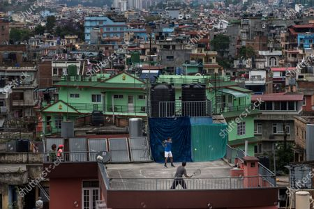 Pranav Manadhar, aged 13, Nepal's U-14 junior national tennis player, plays tennis with his father at the rooftop of his home in Kathmandu, Nepal, 28 April 2020. Nepal is under lockdown in a bid to halt the wide spread of coronavirus.