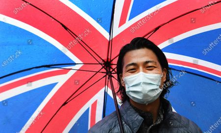 An Asian man holds a Union Flag umbrella in central London, Britain, 28 April 2020. Britons are now in their fifth week of lockdown due to the Coronavirus pandemic. Countries around the world are taking increased measures to stem the widespread of the SARS-CoV-2 coronavirus which causes the Covid-19 disease.