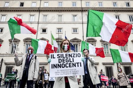 The president of the Fratelli d'Italia (FdI) party Giorgia Meloni (C) with FdI parliamentarians demonstrate against the Italian government in front of the Chigi Palace in Rome, Italy, 28 April 2020. Meloni holds a sign reading 'the silence of the innocent. Representing the thousands of Italians who risk their jobs'. The Italian government announced a gradual lifting of the lockdown restrictions that were implemented to stem the widespread of the SARS-CoV-2 coronavirus that causes the COVID-19 disease, reports state. From 04 May 2020 on, the country's population will be again allowed access to parks and gardens, and to move around their own regions, among others; more restrictions are set to be lifted on 18 May and 01 June 2020.