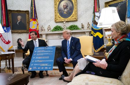United States President Donald J. Trump looks on as Governor Ron DeSantis (Republican of Florida) makes remarks during a meeting in the Oval Office of the White House in Washington, DC,. At right is Dr. Deborah L. Birx, White House Coronavirus Response Coordinator.