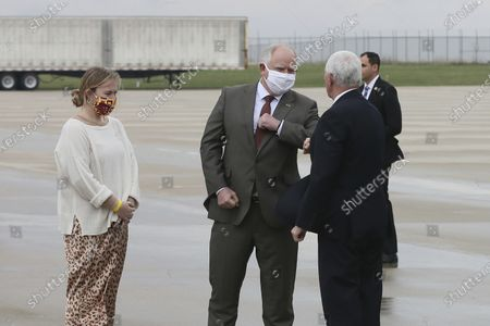 Minnesota Gov. Tim Walz, second from right, greets Vice President Mike Pence with an elbow bump as he arrives for a visit to the Mayo Clinic, in Rochester, Minn., where he toured the facilities supporting COVID-19 research and treatment. Looking on is Lt. Gov. Peggy Flanagan