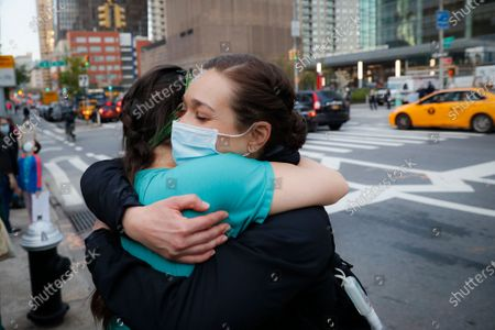 Nurses Julia Bevilaqua, left, and Natalie Mendoza embrace after a nightly 7 p.m. applause for medical personnel during the coronavirus pandemic, outside NYU Langone Medical Center in the Manhattan borough of New York