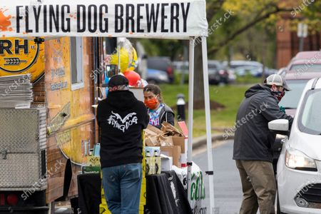 Flying Dog Brewery employee CJ Winpigler, right, hands beer and food into a vehicle during an event with local businesses including Flying Dog Brewery, Roast House Pub, McCutcheons and Frederick Balloons to front line essential workers, including healthcare and first responders in Frederick, Md., . At left are Brandon McGee and Rachel Strickland