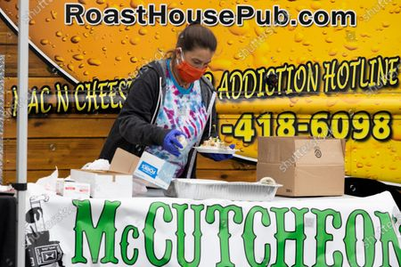 Rachel Strickland of Roast House Pub prepares food during an event with businesses including Flying Dog Brewery and McCutcheons to distribute food and beer to front line essential workers, including healthcare and first responders in Frederick, Md