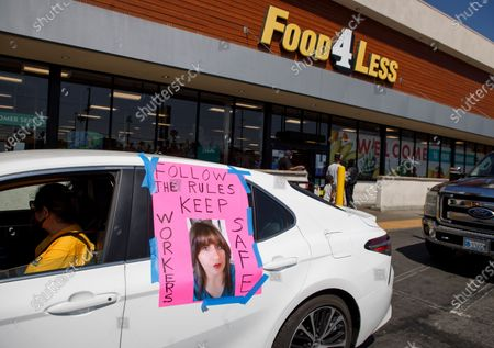 Grocery store workers protest for greater protections agianst coronavirus and COVID-19, outside of a Food 4 Less store in Los Angeles, California USA, 28 April 2020. Protesters displayed a photo of one of the store's workers, Angela Perez, who recently tested positive for COVID-19.