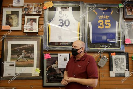 "This, photo shows Jim Bernardini, owner of Lefty's Sports Cards, wearing a mask while interviewed in front of sports memorabilia of athletes Muhammad Ali, Mickey Mantle, Stephen Curry, Kevin Durant and Willie Mays and at his store, which closed for COVID-19 concerns, in Burlingame, Calif. Bernardini, who was forced to lay off three salaried employees and is handling the online sales and shipping department 7 days a week, says their social media presence has helped maintain business but is not close to the walk in traffic of the store, and has had to cancel in-store autograph signings with pro athletes. ""People miss sports and coming into my store to discuss the previous days games and collect their favorite players,"" he says"