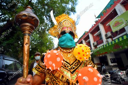 A central government employee Baldev is seen dressed as Yamraj or Hindu god of death, wearing a novel coronavirus-themed balloon necklace, gestures as he poses during an awareness about social distancing and staying at home organised by Delhi police during a nationwide lockdown, at RK Puram, Sector 1