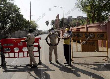 Indian policemen stand guard during the funeral of Bollywood actor Irrfan Khan, outside a graveyard in Mumbai, India, . Khan was a veteran character actor in Bollywood movies and one of India's best-known exports to Hollywood. Khan died Wednesday after being admitted to Mumbai's Kokilaben Dhirubhai Ambani hospital with a colon infection. He was 54