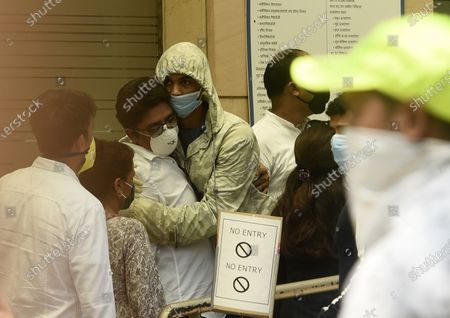 Babil Khan, son of Bollywood actor Irrfan Khan, center right, hugs an unidentified person outside Kokilaben Dhirubhai Ambani hospital after the news of his father's death, in Mumbai, India, . Irrfan Khan, a veteran character actor in Bollywood movies and one of India's best-known exports to Hollywood, died on Wednesday after being admitted to the hospital with a colon infection. He was 54