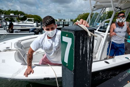 Stock Picture of Alex Gonzalez, (L) moors his boat, after the boat ramps and parks reopening, at the Pelican Harbour Boat Ramp in Miami, Florida, USA, 29 April 2020.  After sitting empty for weeks to prevent the spread of coronavirus, several Miami-Dade and Broward Counties parks are reopening today. The measured reopening begins with parks, boating, and golf. Cities and towns across Miami-Dade and Broward counties have announced which of their parks will reopen after Miami-Dade Mayor and Broward Mayor signed executive orders to allow them to operate under certain restrictions.