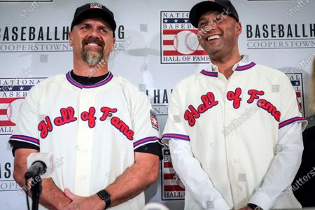 Former New York Yankees shortstop Derek Jeter, right, and former Colorado Rockies outfielder Larry Walker pose after receiving their Baseball Hall of Fame jerseys during a baseball news conference in New York. Jeter and Walker and the rest of this year's Baseball Hall of Fame class will have to wait for their big moment at Cooperstown. The Hall of Fame announced, that it has canceled its July 26 induction ceremony because of the coronavirus outbreak
