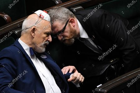 Far-right Confederation leaders Janusz Korwin-Mikke (L) and Grzegorz Braun (R) converse in the meeting room during the second day of the 11th sitting of the Sejm (lower house of parliament) in the Polish Parliament building in Warsaw, Poland, 30 April 2020.