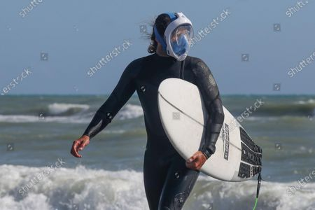 A surfer starts training again wearing a protective mask, even in the sea in Ostia beach