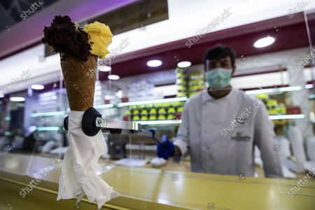 An ice cream vendor wears a protective mask while working in an ice cream shop in the center of Rome, Italy, 30 April 2020. Italy was still under a emergency lockdown due to Covid-19 pandemic.