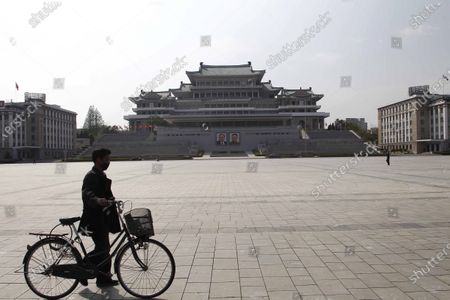 Man walks his bicycle at the Kim Il Sung Square in Pyongyang, North Korea, . Portraits in the background are the late leaders Kim Il Sung, left, and Kim Jong Il
