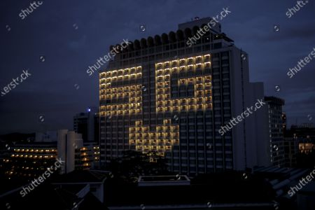 A view on 'SG Love' message made of rooms lights on the facade of the Shangri-La Hotel in Singapore, 30 April 2020. The hotel will light up 121 of its rooms for three and half hours each night till 01 May as a message of support for frontline medical workers and essential workers amid the SARS-CoV-2 coronavirus which causes the Covid-19 disease. .